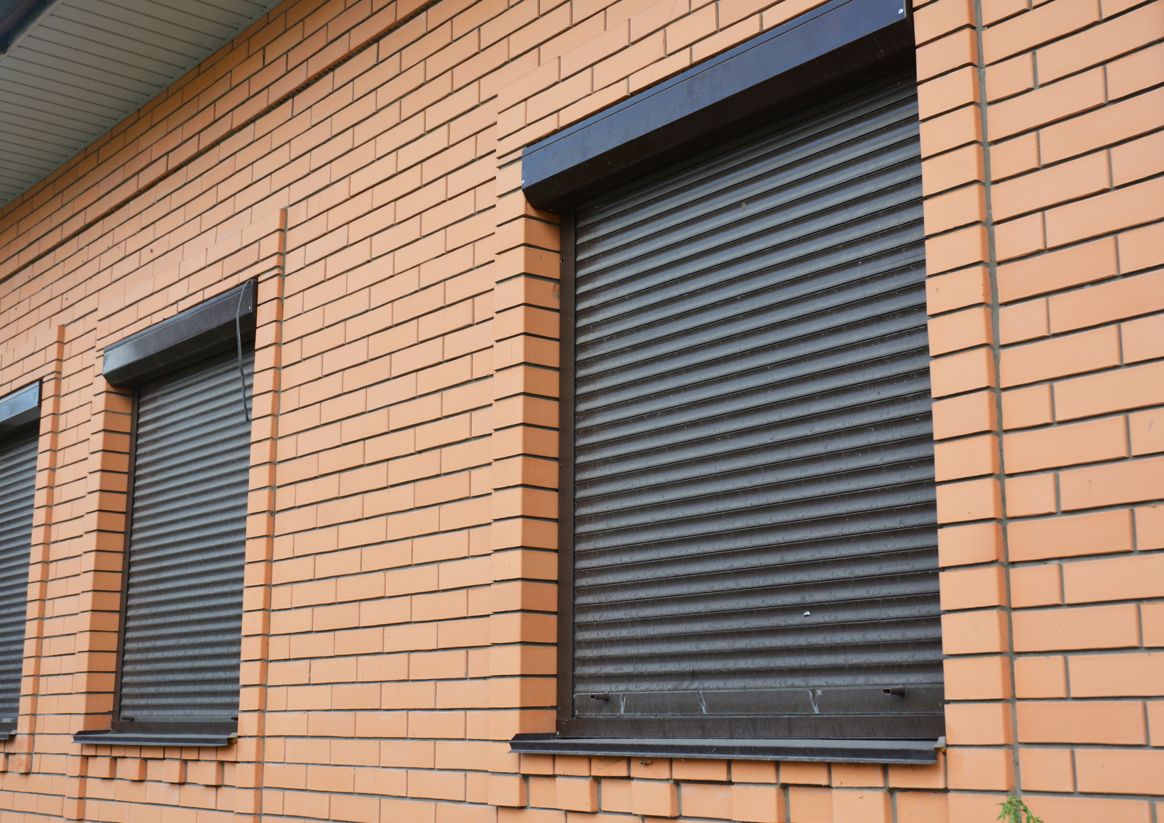 Brick House Windows with rolling shutter for house protection.